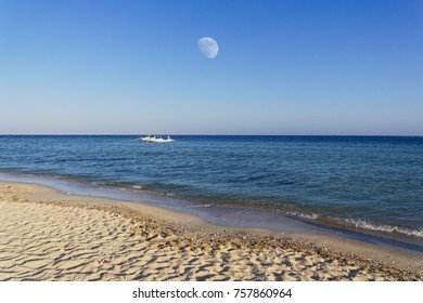 Moon rising over the Red Sea just before sunset. Two local fising boats moored close to the beach.