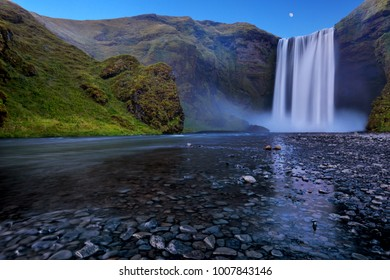 The moon rising over Skogafoss Falls and the river bed, Iceland