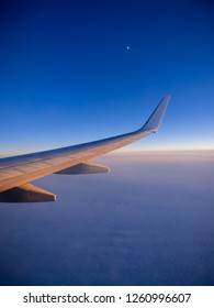 Moon rising over the wing of a passenger plane