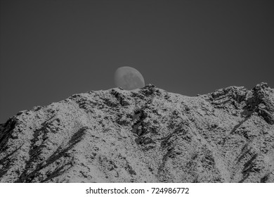moon set over snowy mountains