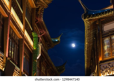 The moon shines between the rooftops of Yuyuan Garden in Shanghai, China.