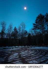 The moon shining over an empty parking lot filled with snow and tire tracks in the forest. This photo was taken at night in the winter in Massachusetts.