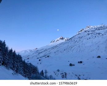 Moon shining oversaw-covered mountains in the Ursern Valley, Hospental, Canton Uri, Switzerland, under a clear blue sky in the early morning.