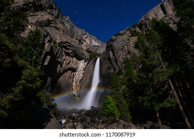 Moonbow or Lunar rainbow and star at Yosemite Upper and Lower Falls during a full moon in Yosemite National Park, California, USA