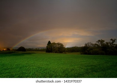 A moonbow (rainbow created by lunar light) above Slovak countryside landscape during a rain shower. Two arches of the moonbow are visible, the lower one is more apparent.