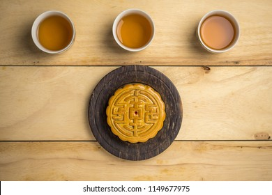 Mooncake with cup of tea flat lay on wooden table, mid autumn festival food.
