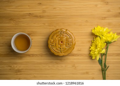 Mooncake with cup of tea and flower flat lay on bamboo table, mid autumn festival food.