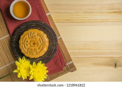 Mooncake with cup of tea and flower flat lay on wooden table, mid autumn festival food with copyspace.