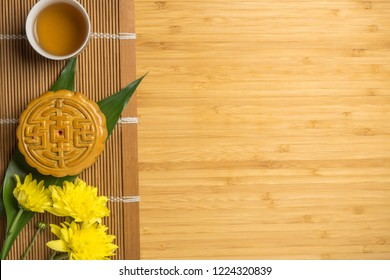 Mooncake with cup of tea and flower flat lay on bamboo table, mid autumn festival food with copyspace.