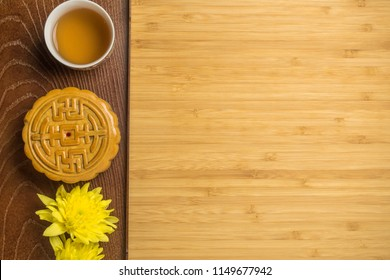 Mooncake with cup of tea and flower in wood tray, flat lay on bamboo table, mid autumn festival concept with copyspace.