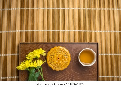 Mooncake with cup of tea and flower in wood tray, flat lay on table, mid autumn festival concept with copyspace.