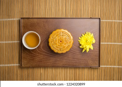 Mooncake with cup of tea and flower in wood tray, flat lay on table, mid autumn festival food.
