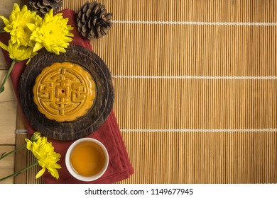 Mooncake with cup of tea, pine cone and flower flat lay on wooden table, mid autumn festival food with copyspace.