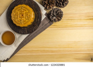 Mooncake with cup of tea and pine cone flat lay on wooden table, mid autumn festival food with copyspace.