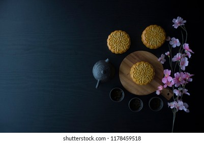 Mooncake flatlay on wooden table. Traditional Baked Mooncake on Dark Background. Mooncakes with Sakura Flowers.