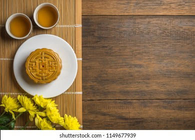 Mooncake on white dish with cup of tea and flower, flat lay on table, mid autumn festival concept with copyspace.