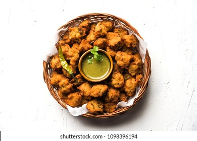 Moong Dal Vada or Pakoda also known as Moongode Served with Green Chutney. selective focus