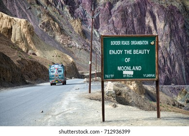 Moonland sign among mountain landscape and truck on road