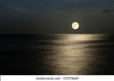 moonlight on the waves at night in the sea on long exposures. The sky, the horizon with the moon in the clouds.