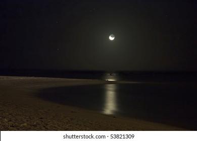 Moonlit beach at night, the moonlight dimly lighting the bay
