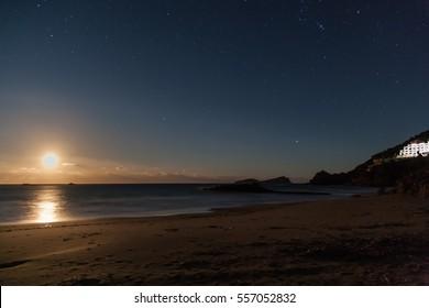 Moonlit beach with night sky