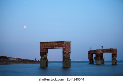 moonrise at longest total eclipse of the moon in 21st century over the old brick pillars of a former landing bridge in the Jadebusen at Eckwarderhoerne, Germany, they look like gates or arches