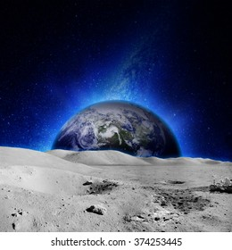 The moon's surface with glowing earth on the background. Elements of this image furnished by NASA.