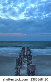 Moonset at Dawn over a dilapidated pier on the beach in Port Royal in Naples, Florida.