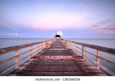 Moonset at Early sunrise over the Naples Pier on the Gulf Coast of Naples, Florida in summer.