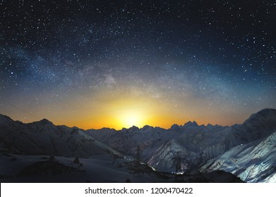 Moonset in the mountains at night with a horizontal milky way on the sky. Snow covered peaks of mountains at night