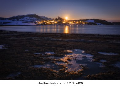 Moonset over Nanclares de Ganboa village in a frozen morning