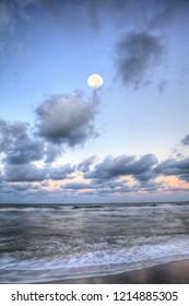 Moonset over the ocean at Vanderbilt Beach at sunset in Naples, Florida