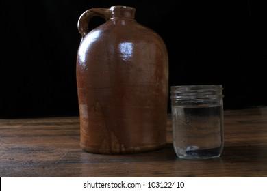 Moonshine corn whisky poured from vintage brown ceramic jug into canning jar sitting on old wooden plank floor against black background.