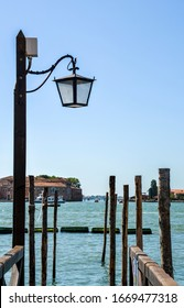 Moorage for gondolas with wooden poles and lamp near San Marco square in Venice