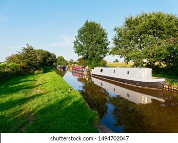 Moored barges in all colours are reflected in the calm water of the Shropshire Union Canal, Llangollen section, by the late afternoon sunlight