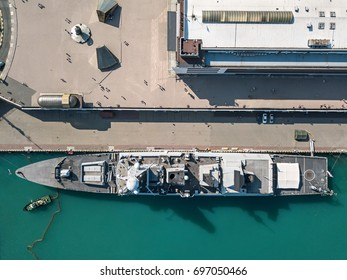 Moored battleship in the dock. On the pier there is a building, people and cars. Top view photo. Horizontal.