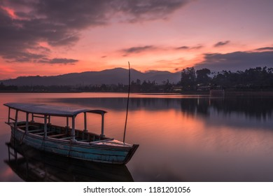 Moored boat on a lake under beautiful sunset