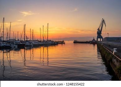 Moored boats and crane on Vilagarcia de Arousa harbor at golden evening