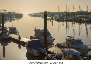 Moored boats on the River Arun at Littlehampton in West Sussex, England. Photographed against setting sun