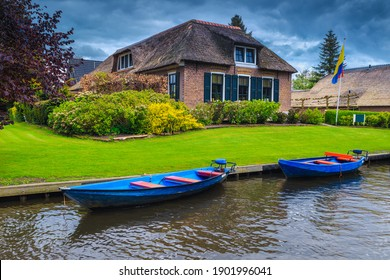 Moored motorboats on the water canal and cute waterfront house with ornamental garden, Giethoorn, Netherlands, Europe