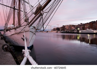 moored sailing yacht in Oslo harbor in pink sunrise light