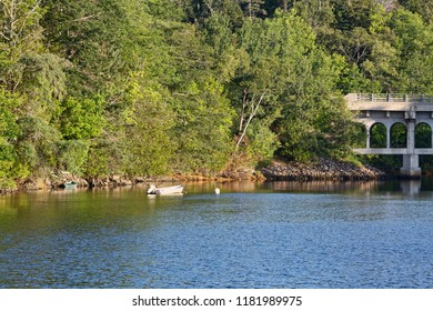 A moored skiff and another tied to the bank of a tidal river with a bridge in the background on the coast of Maine in the summertime.