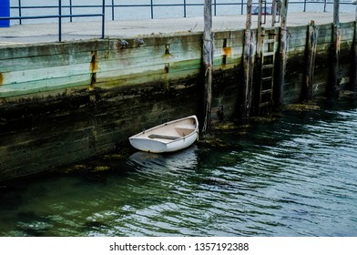 Moored skiff at a pier on the ocean inlet in calm waters.
