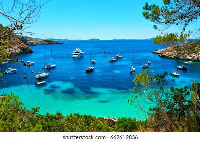 Moored vessels, sailboats, yachts and motorboats at Cala Salada turquoise lagoon cove. Idyllic scenics place for vacationers and summer holidays, bright colours, Ibiza Island, Balearic Islands. Spain