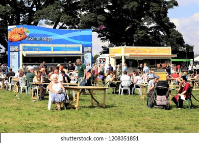 Moorgreen, Nottinghamshire, UK. August 26, 2013.Families relaxing at the  Mobile food and drink stalls on the showground at the Moorgreen country show in Nottinghamshire. UK.