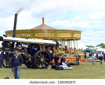 Moorgreen, Nottinghamshire, UK.  August 29, 2011.  Spectators browsing the show whilst workmen prepare the steam engine on the showground at the Moorgreen  show at Moorgreen in Nottinghamshire, UK