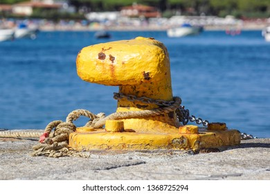 A mooring bollard entwined with a mooring rope. Moored ships at the port quay