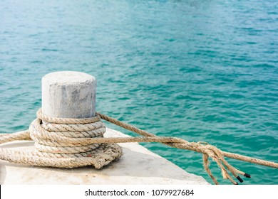 A mooring bollard entwined with a mooring rope at port