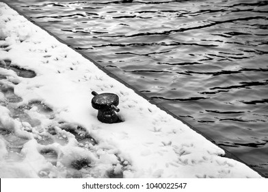 Mooring bollard on a winter pier covered with snow