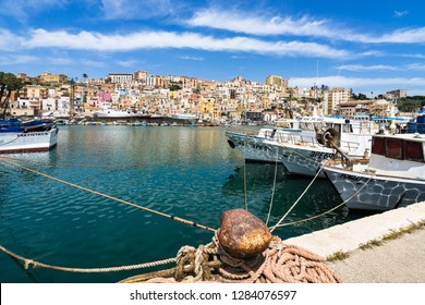 Mooring bollard at Sciacca harbour. Fishing boats on the right and colorful old town buildings on the background. Sciacca, Sicily, Agrigento province, Italy, May 2018